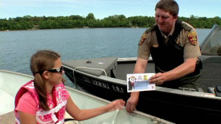 Image of a conservation officer handing a child a certificate for cool treat at Dairy Queen for wearing their life jacket while boating.