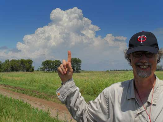 Fred pointing to a large storm cloud on the horizon.