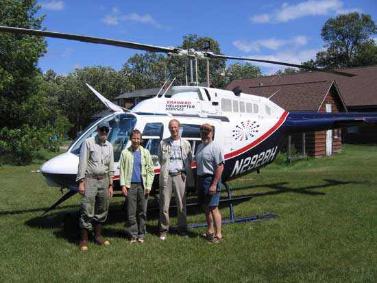 Four individuals, the peatland survey group, standing in front of a helicopter in the town of Waskish.