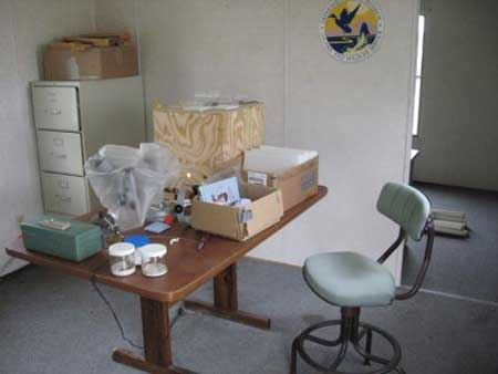 Wooden table with boxes and extraction tools on top of it in a room with a file cabinet and a blue chair.