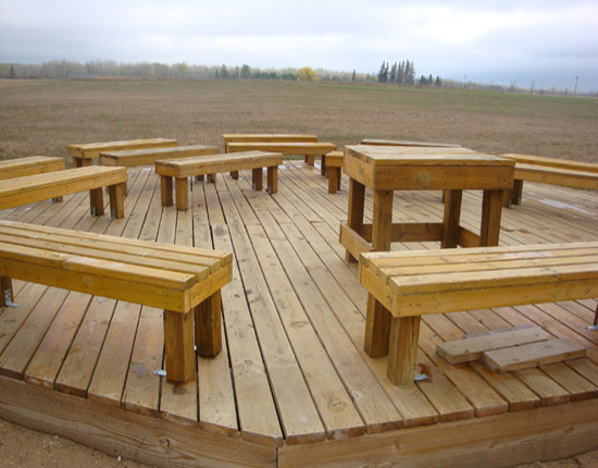 Wooden platform, benches, and teaching podium located in the Baudette School Forest, Baudette.