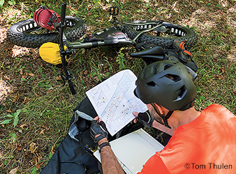 image of biker looking at a map.